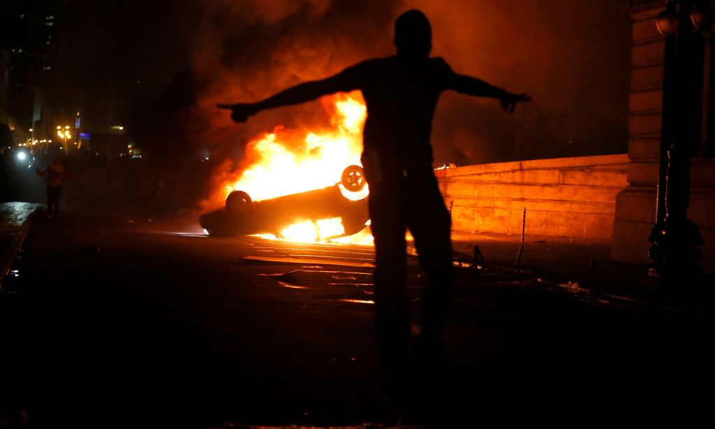 A demonstrator celebrates by a burning car in downtown Rio de Janeiro